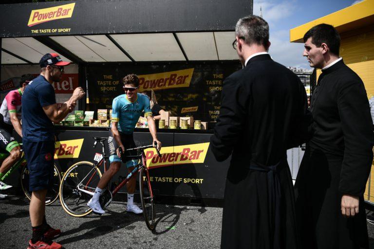 Los sacerdotes observan mientras el danés Jakob Diemer Fuglsang (L) recoge bocadillos en la aldea de inicio en Lourdes (Getty Images)